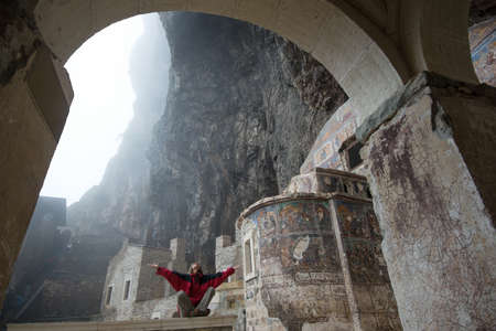 enhances: Woman dressed in red clothes meditates in Sumela Monastery Turkey. Foggy weather enhances spiritual discipline effect.