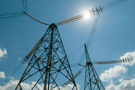 sun energy: High-voltage power line against the blue sky with white clouds and sun. Idea - electricity is energy, sun also gives energy.