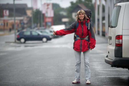 woman stop: Woman - hitchhiker. Woman is dressed in bright red clothes and has a backpack on herself.