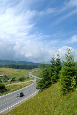 the carriageway: Gray bus is moving along the asphalt road with carriageway marking. The road is surrounded with fields, meadows and forest. Fir-tree and grass are in the foreground, blue sky with clouds are in the backgrpound.