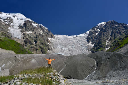 icefall: Happy tourist against large icefall background. Summer clear day and beautiful nature.