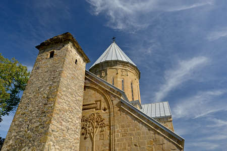 stillness: Ananuri church and fortress tower against beautiful sky background.  Cirrus clouds  become the stillness of the sky. Plant stone decoration is seen on church front.