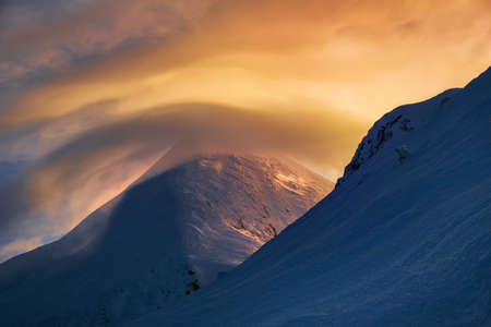 winter dance: Enchanting color spectacle in winter mountains - red-ene-yellow clouds dance round the mount. Dark snow surface contrasts with bright clouds.