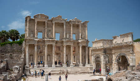 splendour: Highly decorated  front of Celsus Library in Ephesus is outlined against blue sky background. Little people figures accentuate architecture splendour.