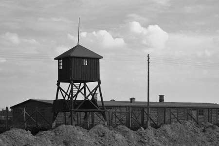 entanglement: Old watchtower, barracks and wire entanglement - Majdanek or KL Lublin concentration camp. Now - memorial. Black-and-white image.