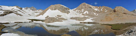 tableland: Mountains with snow and blue sky is reflected in the lake. Panorama of Adigol table-land Aladaglar Mountains, Turkey.