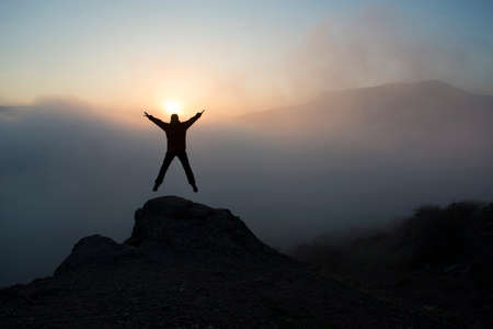 contemplates: Woman jumps and lifts her arms in victory. She contemplates beautiful sunset in mountains.