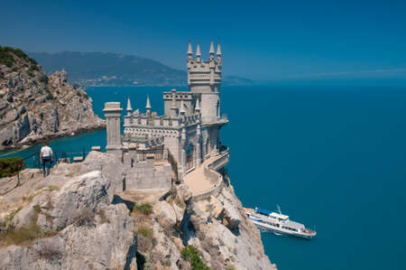 alupka: Landmark Swallows Nest located in Gaspra: between Yalta and Alupka on the Crimean peninsula.  Beautiful building is situated on rock against blue sea and sky background. Stock Photo