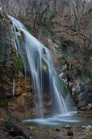 inclusions: Djur-Djur waterfall Crimea Mountains. Snow inclusions and icicles may be seen on the photo. Waterfall is surrounded with leafless forest. Stock Photo