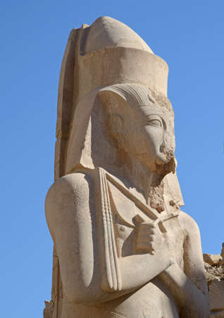 greatness: Ramses II statue close-up against blue sky background. Place - Karnak complex in Luxor Egypt. Monuments of former greatness.