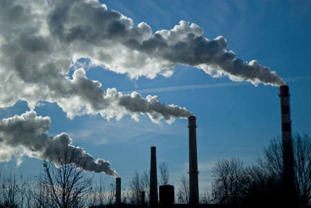 CO2 emissions: Industrial smoke is illuminated with sun. Dark plant tubes and smoke are outlined against blue sky background.