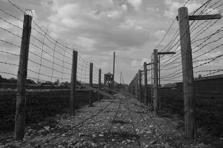 morose: Two rows of barb-wire fence in  Majdanek concentration camp. Black-and-white color range emphasizes morose of buildings.