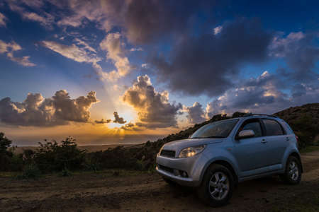 crossover: Gray car (crossover utility vehicle) on ground road against beautiful sea sundown. Editorial