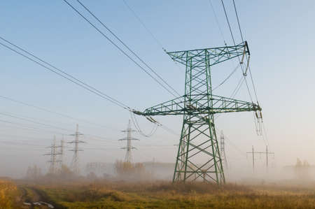 shrouded: Electricity transmission lines are associated to landscape. Industrial constructions are shrouded in morning mist.
