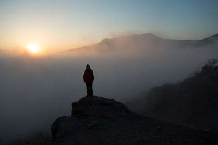 remoteness: Tourist silhouette against sunset scene in mountains.