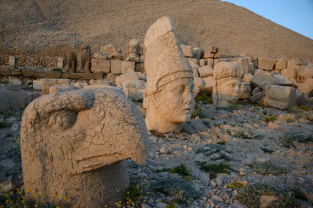 Some of the statues near Mount Nemrut (Turkey). West Terrace: heads of God Apollon, Goddess of Kommagene (Tyche) and God Ptah. Scene in the sunset sun. Stock Photo - 56404559