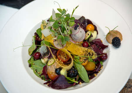 plantlet: Bright multicolored salad on white dish. Salad contains fresh vegetables, spices and berries. Stock Photo