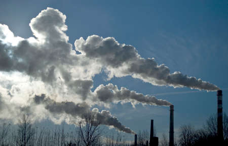 co2 emissions: Factory tubes and white smoke against blue sky. Industrial scene. Stock Photo