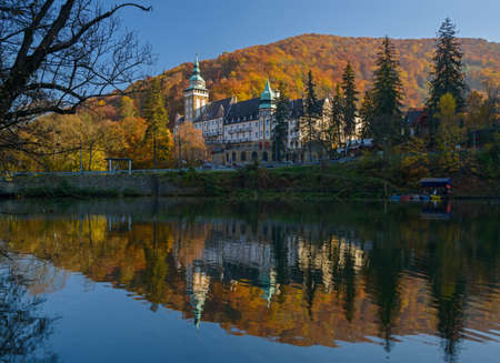 Northern front of Lillafured palace (Miskolc, Hungary). Lake Hamori in foreground, mountains covered with multicolored forest in background. Stock Photo - 56387485