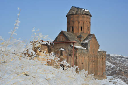 Old armenian church with skewed roof. Snow and frosted plants in foreground. Famous Saint Gregory (Tigran Honents) church in Ani (now - Turkey).