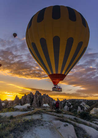 Flying hot-air balloons against sunrise sky background. Photographer is making photo about Cappadocia.
