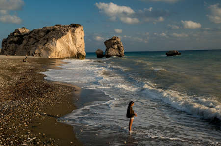 Illuminated with evening sun Aphrodites Rock (Petra tou Romiou  or Rock of the Greek - Cyprus) against beautiful sky. Beach, waves and girl in foreground. Stock Photo