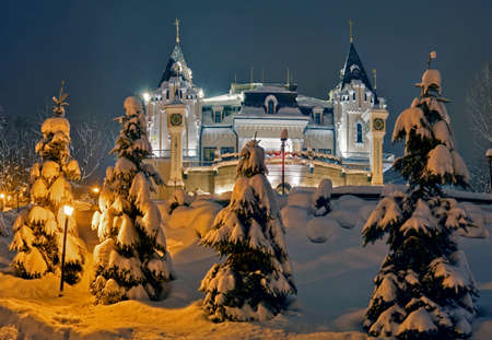 Illuminated Kiev Puppet Theatre. Snowy fir-trees in foreground.