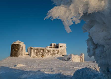 Frosted old Polish observatory on Pop Ivan Mount (Ukraine) against blue sky background. Little man form shows lardge building size. Reklamní fotografie - 69670689