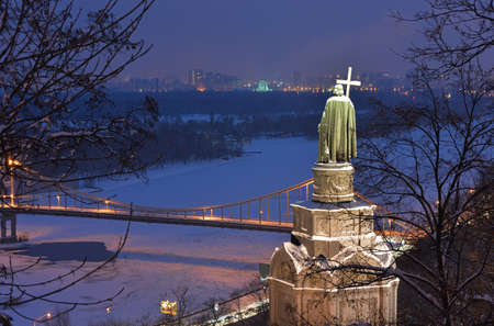 Illuminated bronze statue of Saint Vladimir in Kiev. Monument is powdered with snow. Frozen Dnieper river and foot bridge in the middle of composition.