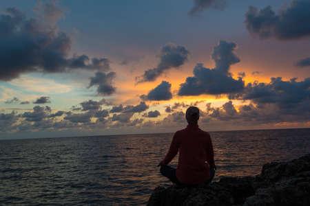 Woman sits as yogi against beautiful sunset over sea background. Reklamní fotografie