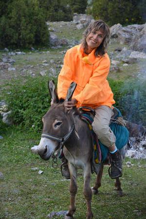 Smiling woman dressed in orange anorak is sitting on donkey. Travel scene.