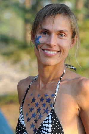 bodyart: Example of body art: smiling woman with painted body. Outdoor scene.
