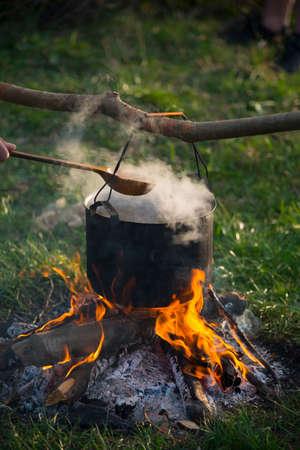 La olla trasera se calienta bajo fuego. Alguien está sosteniendo una gran cuchara de madera debajo de la olla. Escena de viaje.