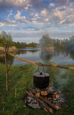 outdoor fireplace: Black pot are heating under fire. Water, trees and sky in background. Stock Photo