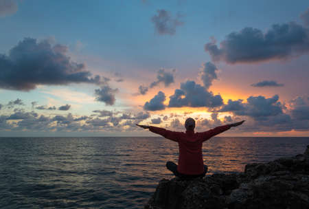Woman (or man) sits as yogi with outstretched hands and contemplates beautiful sunset over sea. Banco de Imagens