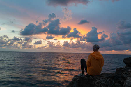 Woman sits on rock and contemplates sunset over sea. Banco de Imagens