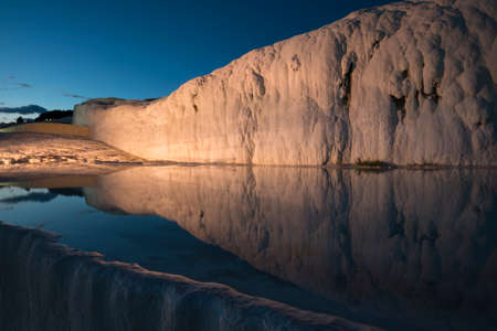 geological formation: Evening illumination in Pamukkale (Turkey). White mountain is reflected in pool water. Blue sky in background.