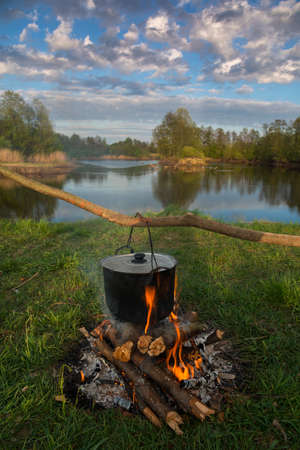 La olla negra se calienta bajo fuego. Escena de viaje.