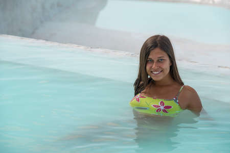 Girl (woman) in natural blue swimming pool. Place - Pamukkale (Turkey).