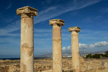 Ancient columns with ionic capitals against blue sky with clouds background. Salamis city ruins, Northen Cyprus.