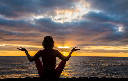 Woman sits as yogi with outstretched hands and contemplates beautiful sunrise over sea (ocean). Banco de Imagens