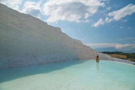 Das Mädchen im hellen Badeanzug ist im azurblauen Travertinpool Pamukkale. Himmel, Wolken, Felder im Hintergrund.
