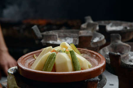 Tajine with vegetables cooking on charcoil.