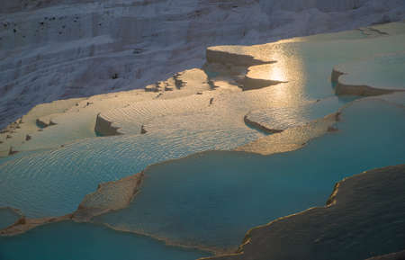Sunlit blue and golden Pamukkale travertines over view.