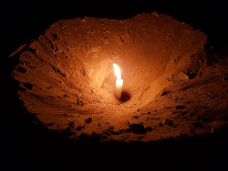 Hollow is made in the sand and a candle burns in it.