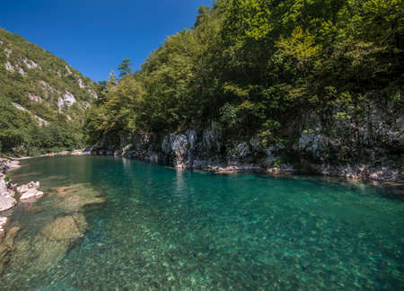 Transparent water in Tara canyon. Green trees are covered mountain slopes. 写真素材