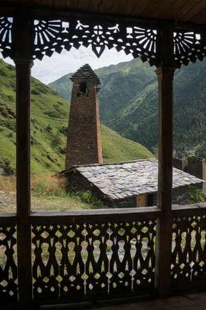 Tusheti Ruderer Blick durch Maßwerk Holzveranda. Grüne Berge im Hintergrund. Standard-Bild