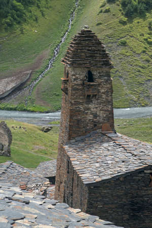 Defensive Tower (Dartlo) against green mountain background. From above it can be seen that all the roofs are made of flat stone, which was traditional for Georgia. Imagens