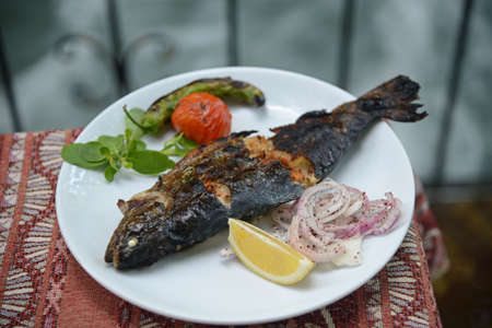 Grilled Fish on white dish with tomato, chopped onion, a slice of lemon, hot pepper and greens.