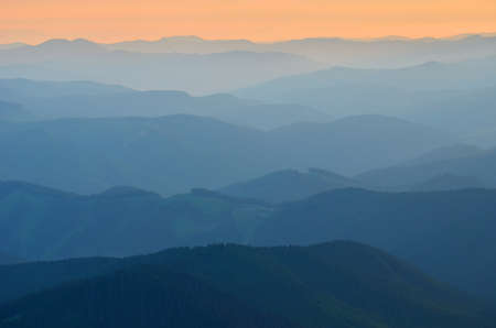 Mountains silhouettes are seen through morning fog. Orange sky in background. Stock Photo